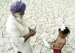 A Sikh farmer prays with his grandson for rains in the district of Fatehgarh Sahib in the northern state of Punjab July 22, 2002. After a spell of rain in northern Punjab and the Indian capital over the weekend farmers in some parts of the state are still hoping that the monsoon rains will arrive. REUTERS/Dipak Kumar